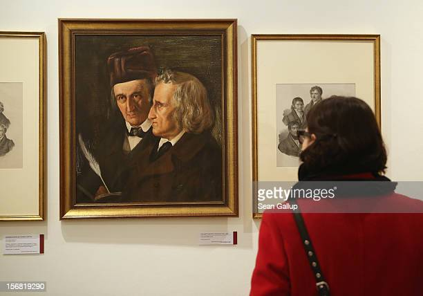 A museum administration employee at the request of the photographer looks at a painting of brothers Jacob and Wilhelm Grimm at the Grimm Brothers...