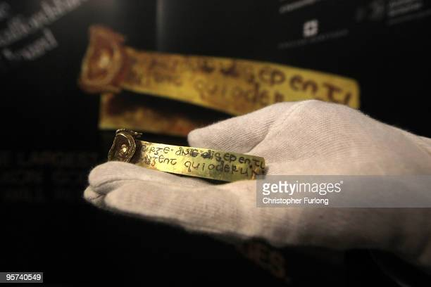 A museum assistant holds a strip of gold bearing a Latin Biblical inscription as historian Dr David Starkey launches the campaign to keep the...