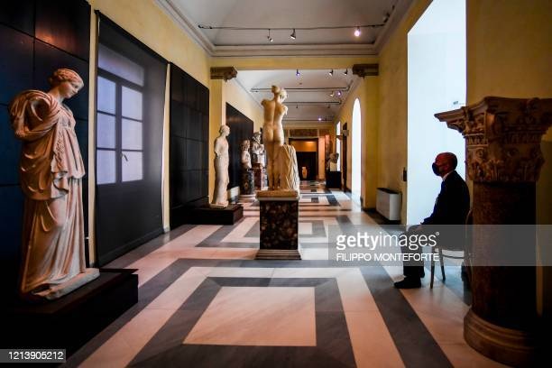 Museum attendant wearing a face mask sits in a room at the Capitoline Museum on Capitoline Hill in Rome as the museum reopens on May 19, 2020 while...