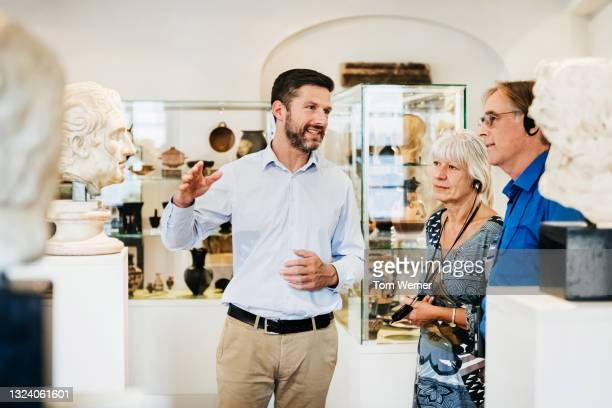museum curator explaining exhibit to visitors - statue stock pictures, royalty-free photos & images