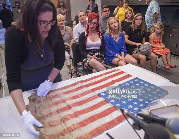 Museum Curator Kyra Schuster carefully unfolds a flag created by prisoners of the WWII Langenstein concentration camp 70years ago as surviving family...