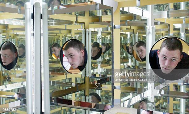 Museum employee Andreas Nitzschke tries out a cube fitted with mirrors intitled 'A view into infinity' at the Jena Optics Museum 15 January 2004 The...