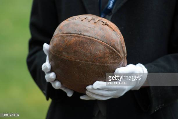 A museum employee holds 'The Somme Football' which was used by British soldiers during the First World War during an event to commemorate England...