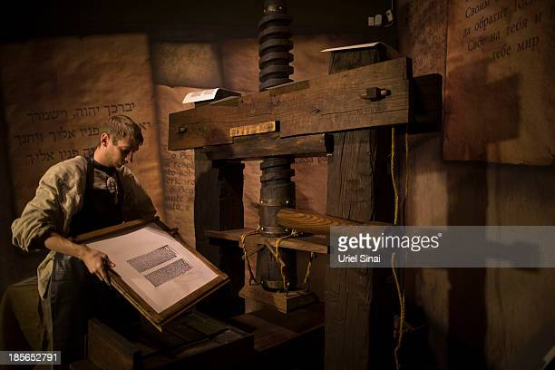 A museum employee shows how a Johannes Gutenberg replica printing press is used at the Book of Books exhibition in the Bible Lands Museum on October...
