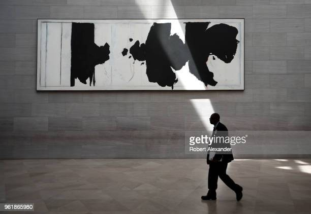 A museum guard walks past a painting by Robert Motherwell titled 'Reconciliation Elegy' as a beam of sunlight strikes the wall at the National...
