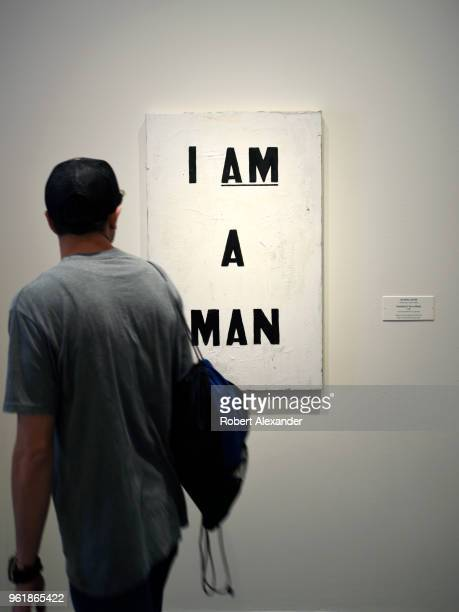 A museum looks at a 1988 painting by Glenn Ligon titled 'I Am a Man' at the National Gallery of Art East Building on the National Mall in Washington...