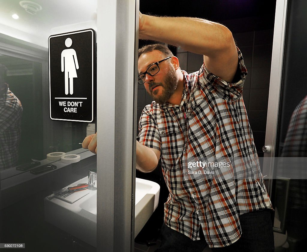 Museum manager Jeff Bell adheres informative backing to gender neutral signs in the 21C Museum Hotel public restrooms on May 10, 2016 in Durham, North Carolina. Debate over transgender bathroom access spreads nationwide as the U.S. Department of Justice countersues North Carolina Governor Pat McCrory from enforcing the provisions of House Bill 2 that dictate what bathrooms transgender individuals can use.