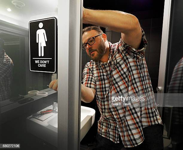 Museum manager Jeff Bell adheres informative backing to gender neutral signs in the 21C Museum Hotel public restrooms on May 10 2016 in Durham North...