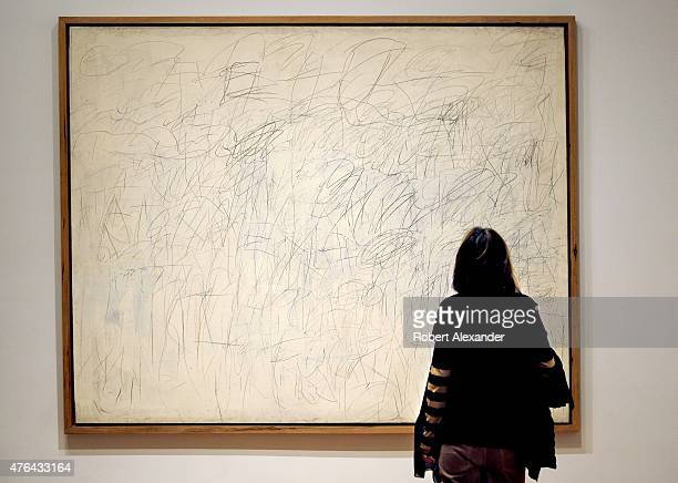 Museum of Modern Art visitor looks at a painting by Cy Twombly titled 'Academy' painted in 1955 on display at the museum in Midtown Manhattan in New...