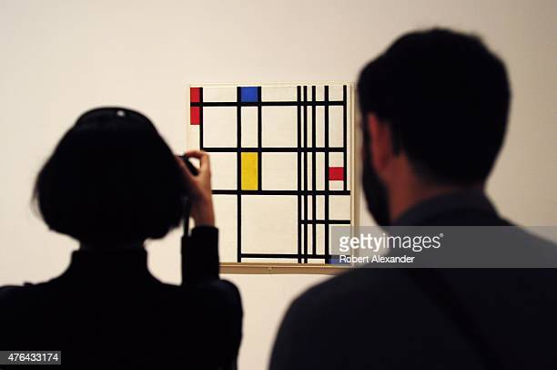 Museum of Modern Art visitors look at a painting by Piet Mondrian titled 'Composition in Red Blue and Yellow' painted in 1937 on display at the...