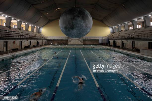 'Museum of the Moon' by British installation artist Luke Jerram is suspended above swimmers at Piscina Cozzi on June 15 2019 in Milan Italy 'Museum...