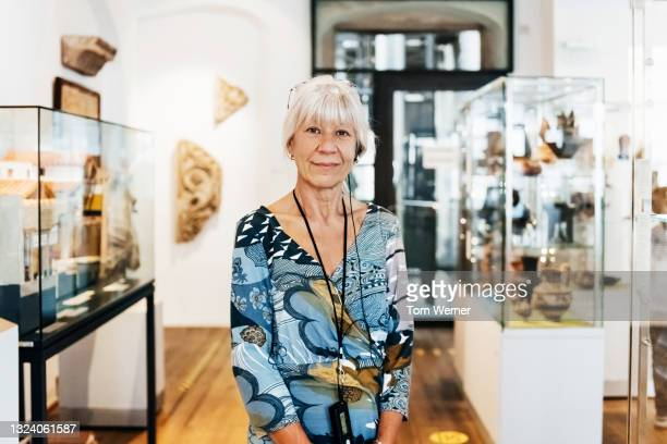 museum patron standing among various exhibits - fringe dress stock pictures, royalty-free photos & images