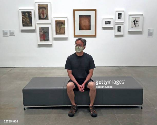 Museum patron wearing a mask sits on a bench in the Beyond Infinity: Contemporary Art after Kusama exhibit at the Institute of Contemporary Art in...