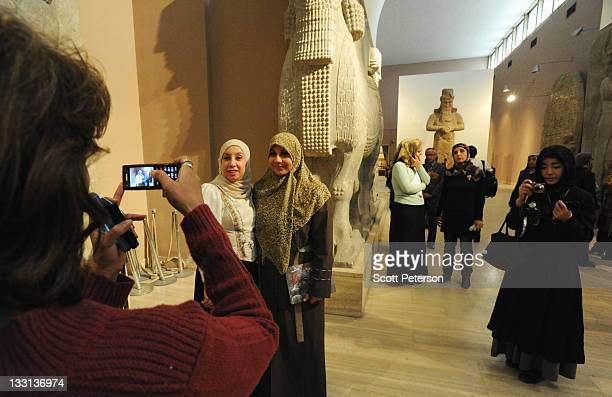 Museum staff take photographs of each other as Iraqi tourism and antiquities officials and French Embassy sponsors open an exhibit about the earliest...