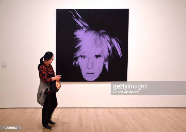 SAN FRANCISCO CALIFORNIA SEPTEMBER 16 2018 A museum visitor admires a 1986 painting titled 'SelfPortrait' by Andy Warhol at the San Francisco Museum...