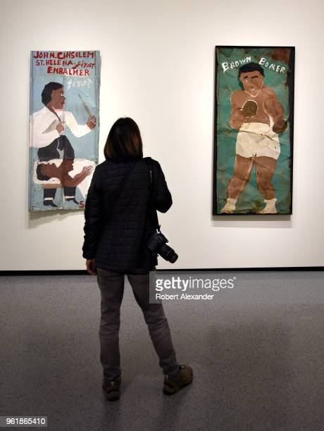 A museum visitor admires two paintings by Sam Doyle at the National Gallery of Art East Building on the National Mall in Washington DC Both were...