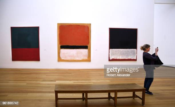 A museum visitor takes a photograph in an exhibit room featuring paintings by Mark Rothko at the National Gallery of Art East Building on the...