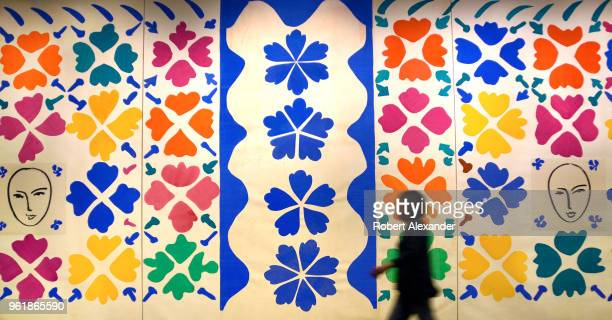 Museum visitor walks in front of a Henri Matisse paper 'cut out' collage titled 'Large Composition with Masks' at the National Gallery of Art East...