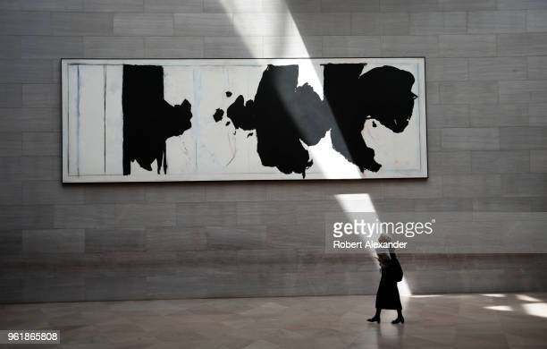 A museum visitor walks past a painting by Robert Motherwell titled 'Reconciliation Elegy' as a beam of sunlight strikes the wall at the National...