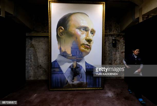 A museum's cleaner walks past a painting depicting Russian president Vladimir Putin at the 'SUPERPUTIN' exhibition at UMAM museum in Moscow on...