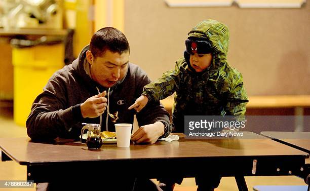 Musher Mike Williams Jr has breakfast in the company of twoyearold Karson Alexie in the school cafeteria at the Nikolai checkpoint during the 2014...