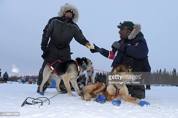 Musher Mike Williams Jr left hands his vet book to veterinarian Bruce Nwadike at the Nikolai checkpoint during the 2014 Iditarod Trail Sled Dog Race...
