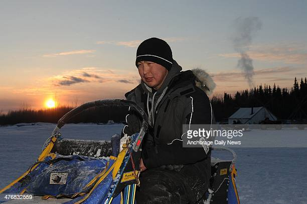 Musher Mike Williams Jr sits on his dog sled as he changes batteries in his headlamp at the Nikolai checkpoint during the Iditarod Trail Sled Dog...