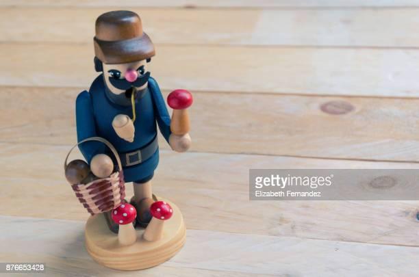 Mushroom finder figurine on wooden background