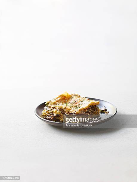 Mushroom lasagne on dark plate on white surface