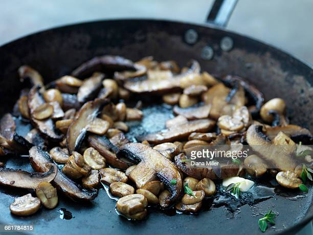 Mushrooms frying in butter in frying pan, close-up