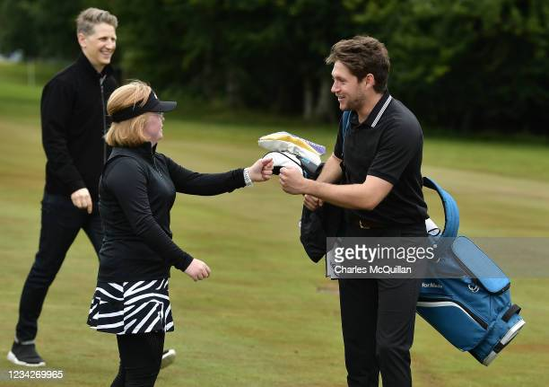 Music artist Niall Horan fist bumps Amy Bockerstette during the Pro Am event at The ISPS HANDA World Invitational at on July 28, 2021 in Ballymena,...