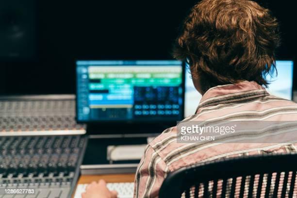 music artist singer recording song at professional music studio using sound mixer - produzent stock-fotos und bilder