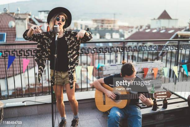 music band performing on rooftop party - singer stock pictures, royalty-free photos & images