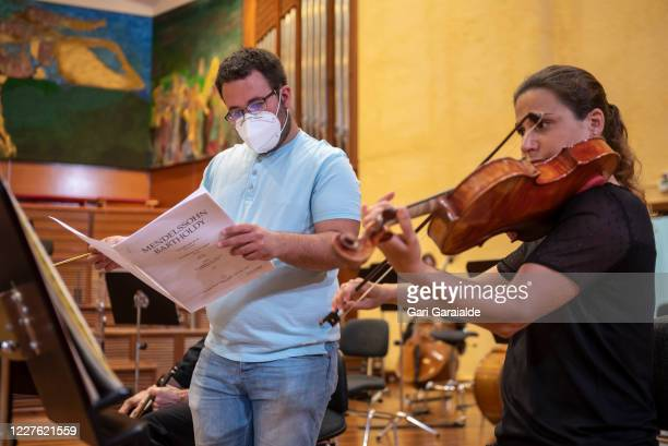 A music by the Basque Symphony Orchestra compares the annotations on the scores while a violinist plays her violin before the concert that will be...