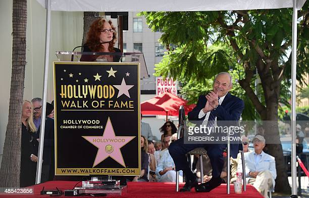 Music executive Joe Smith applauds as musician Bonnie Raitt addresses the audience during Smith's Hollywood Walk of Fame Star ceremony in Hollywood...