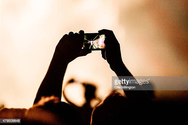 A music fan in the crowd taking a photograph with a camera phone on Day 2 of New Look Wireless Festival at Finsbury Park on July 4 2015 in London...