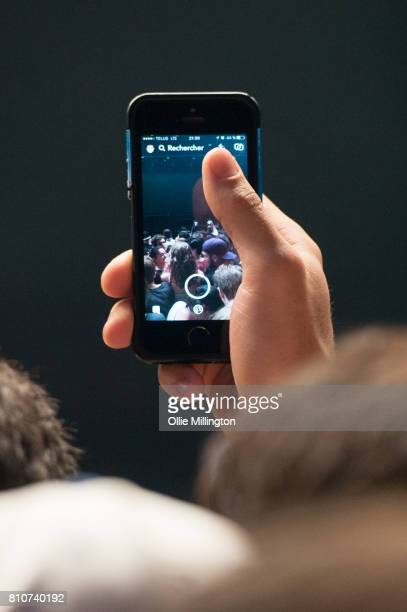 A music fan using their phone in the crowd as Kendrick Lamar performs onstage headlining Day 2 of the 50th Festival D'ete De Quebec on the main stage...