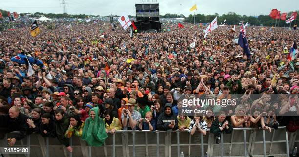 Music fans cheer as Amy Winehouse performs on the Pyramid Stage at Worthy Farm Pilton near Glastonbury on June 22 2007 in Somerset England The...