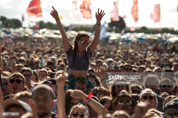 Music fans cheer as the band Haim perform on the Other Stage at the Glastonbury Festival of Music and Performing Arts on Worthy Farm near the village...