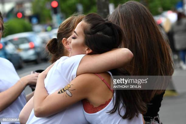 Music fans embrace outside the Old Trafford Cricket Ground ahead of the One Love Manchester tribute concert in Manchester on June 4 2017 Nearly two...
