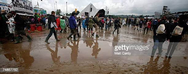 Music fans in wellies walk in the mud as they wait for a band on the Pyramid Stage Adjegas open the festival at Worthy Farm Pilton near Glastonbury...