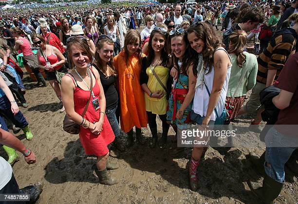 Music fans in wellies walk in the mud in front of the Pyramid Stage Adjegas open the festival at Worthy Farm Pilton near Glastonbury on June 22 2007...