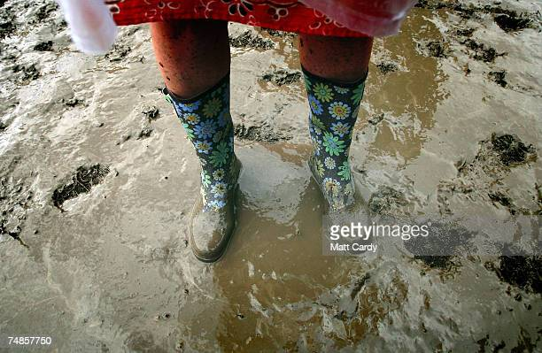 Music fans in wellington boots walk in the mud as they wait for a band on the Pyramid Stage at Worthy Farm Pilton near Glastonbury on June 22 2007 in...