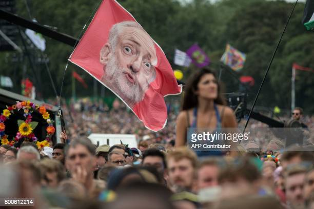 Music fans listen as Jeremy Corbyn Leader of the Labour Party addresses the crowd from the Pyramid Stage during the Glastonbury Festival of Music and...