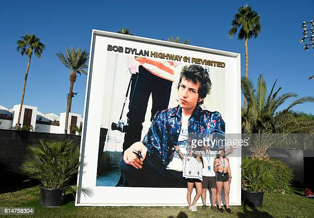 Music fans pose in front of the Bob Dylan 'Highway 61 Revisited' album cover displayed on the grounds at Desert Trip at The Empire Polo Club on...