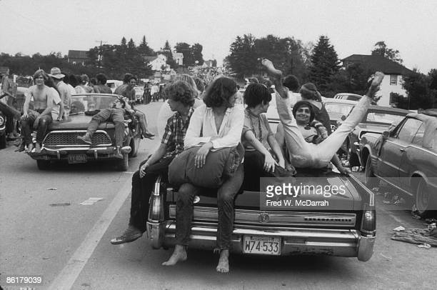 Music fans sit on the hoods of cars on the crowded roads near the Woodstock Festival Bethel New York between August 1517 1969