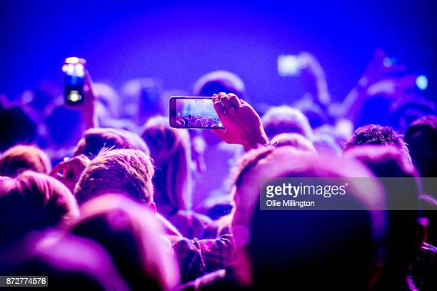 Music fans take photographs with mobile phones as Thomas Rhett performs at The Roundhouse on November 10 2017 in London England