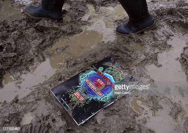 Music fans walk past a discarded 2011 festival program as they arrive in the mud and the rain at the Glastonbury Festival site at Worthy Farm, Pilton...