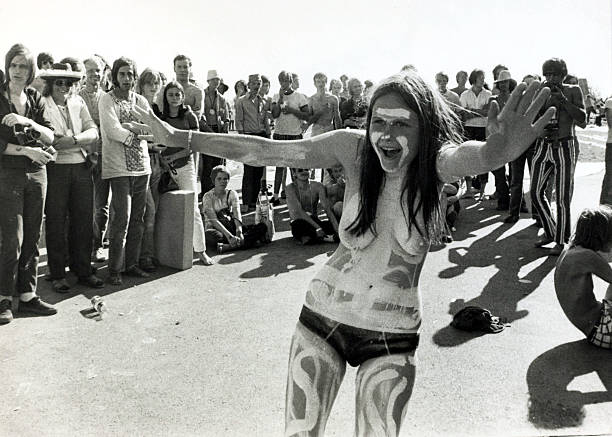 Music Festivals pic: 22nd June 1970. A young woman topless and covered in body paint draws onlookers at the Music Festival of the Rising Sun at Mantorf, Sweden.