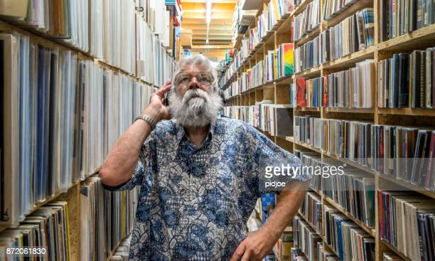 music lover surrounded by his vinyl album collection. with headset on, in front of his collection - ver a hora imagens e fotografias de stock